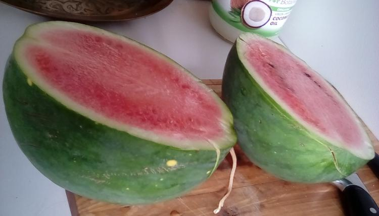 Weeks NC Giant cross watermelon fruit with stars, sliced in two, on a cutting board. It has pink flesh and dark seeds. The rind has stripes.